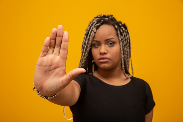 Mujer afroamericana joven que muestra la mano en señal de que se detengan con prejuicios raciales.