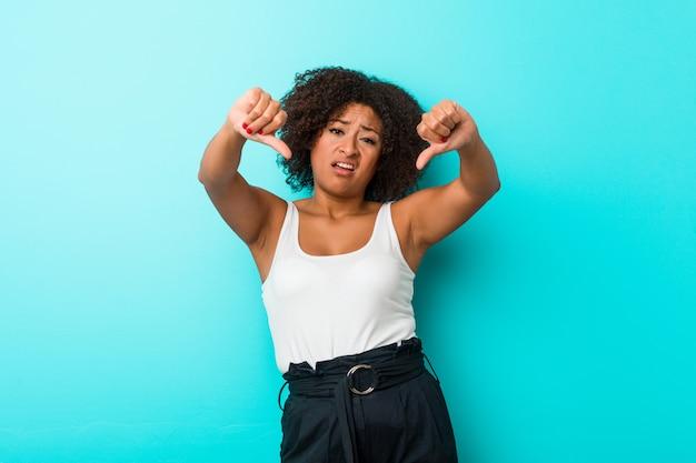 Mujer afroamericana joven que muestra el pulgar hacia abajo y que expresa aversión.