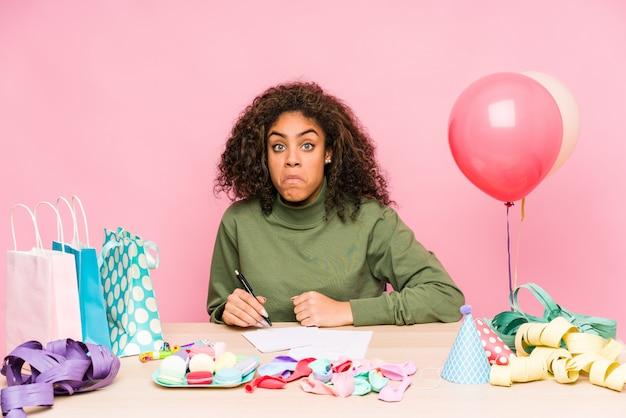 La mujer afroamericana joven que planea un cumpleaños se encoge de hombros y abre los ojos confundidos.