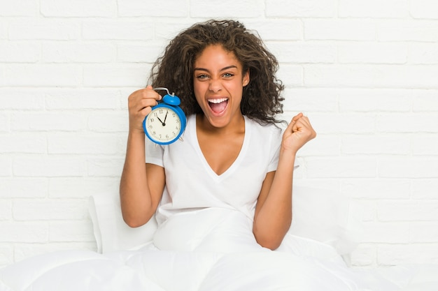 Mujer afroamericana joven que se sienta en la cama que sostiene un despertador que anima despreocupado y emocionado. concepto de victoria