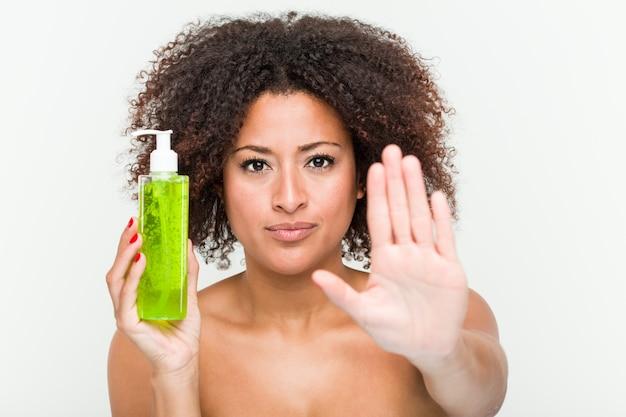 Mujer afroamericana joven que sostiene la botella del áloe vera que se coloca con la mano extendida que muestra la señal de stop, previniéndole.