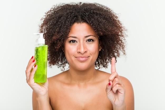 Mujer afroamericana joven que sostiene la botella del áloe vera que muestra el número uno con el dedo.