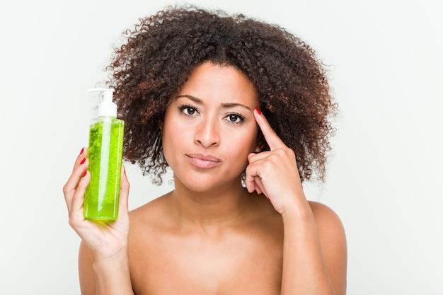 La mujer afroamericana joven que sostiene la botella del áloe vera que señala su templo con el dedo, pensando, se centró en una tarea.