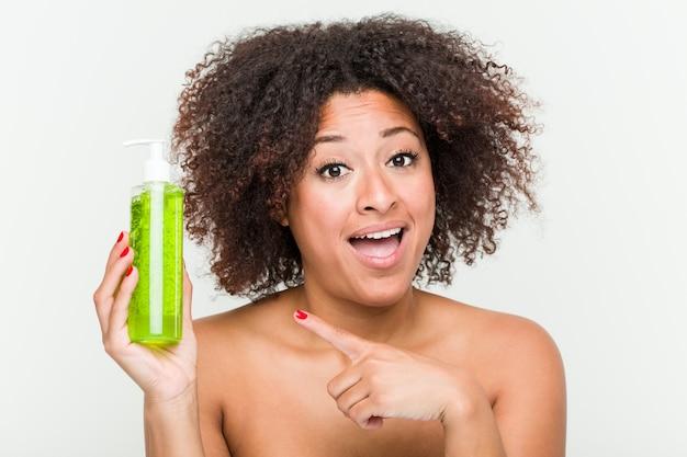 Mujer afroamericana joven que sostiene la botella del áloe vera que sonríe alegremente que señala con el índice lejos.