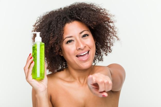 La mujer afroamericana joven que sostiene la botella del áloe vera sonríe alegre que señala al frente.