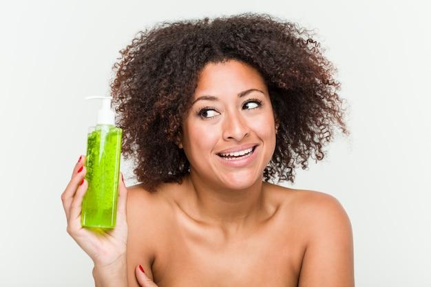 Mujer afroamericana joven que sostiene la botella de aloe vera sonriendo confiado con los brazos cruzados.