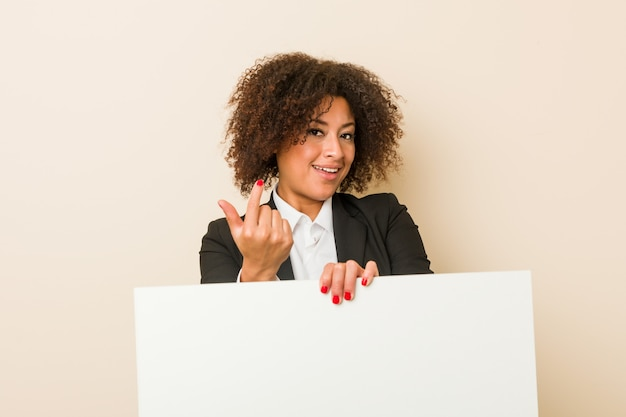 La mujer afroamericana joven que sostiene un cartel que señala con el dedo a usted como invitando se acerca.