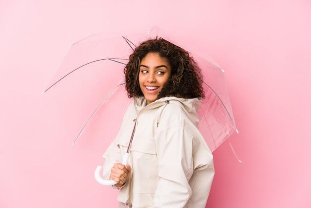 La mujer afroamericana joven que sostiene un paraguas mira a un lado sonriente, alegre y agradable.