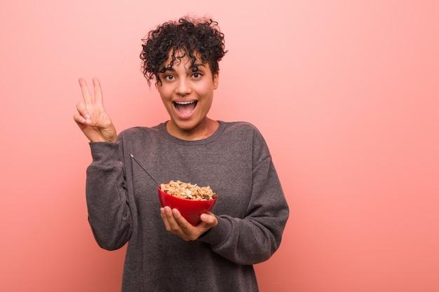 Mujer afroamericana joven que sostiene un tazón de cereal que muestra el número dos con los dedos.