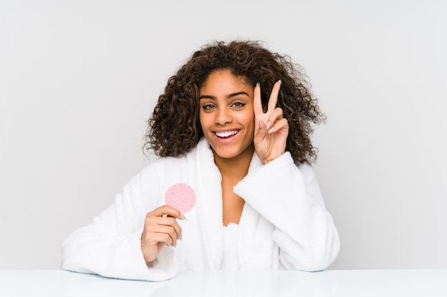 Mujer afroamericana joven que usa un disco facial que muestra la muestra de la victoria y que sonríe ampliamente.