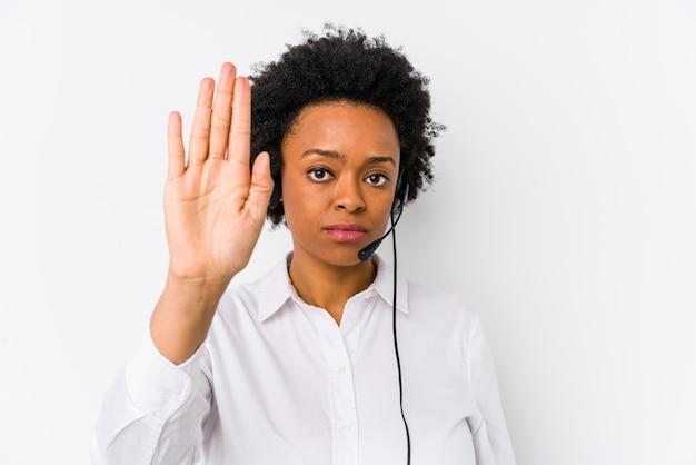 Mujer afroamericana joven del telemarketer que se coloca con la mano extendida que muestra la señal de stop, previniéndole.