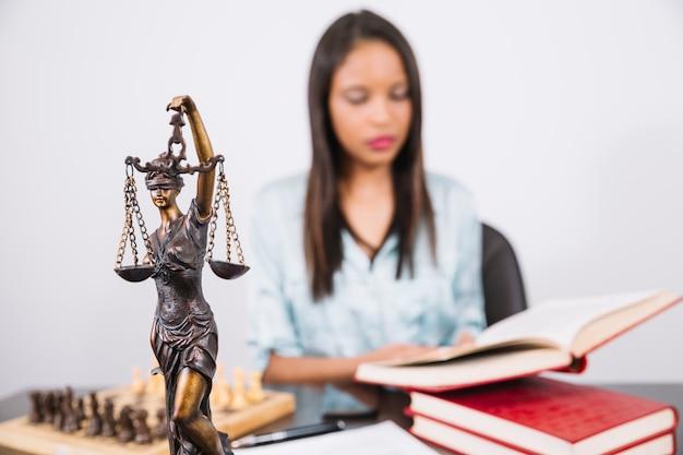 Mujer afroamericana con libro en mesa cerca de ajedrez, teléfono inteligente y estatua