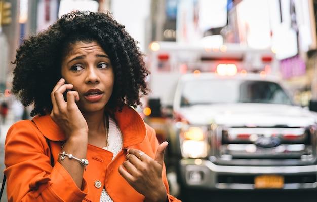 Mujer afroamericana llamando al 911 en la ciudad de nueva york. concepto sobre accidentes automovilísticos y emergencias