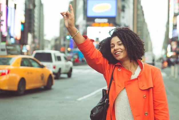 Mujer afroamericana llamando a un taxi en nueva york