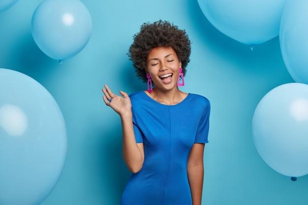 La mujer afroamericana llena de alegría cierra los ojos con alegría, usa un elegante vestido azul, modela sobre globos festivos, posa durante la celebración, tiene humor de fiesta la cumpleañera se mueve con ritmos de música