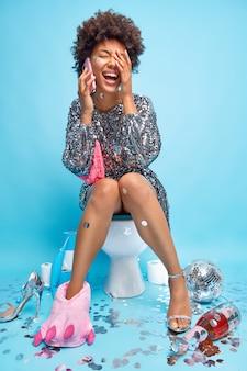 Una mujer afroamericana llena de alegría tiene una conversación telefónica hace una llamada telefónica mientras defeca en la taza del inodoro rodeada de una bola de discoteca de confeti y una botella de champán pasa el tiempo libre en el baño