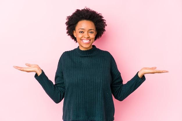 Mujer afroamericana de mediana edad contra un fondo rosa aislado hace escala con los brazos, se siente feliz y segura.