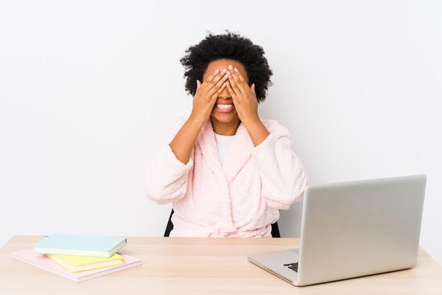 La mujer afroamericana de mediana edad que trabaja en casa aislada cubre los ojos con las manos, sonríe ampliamente esperando una sorpresa.