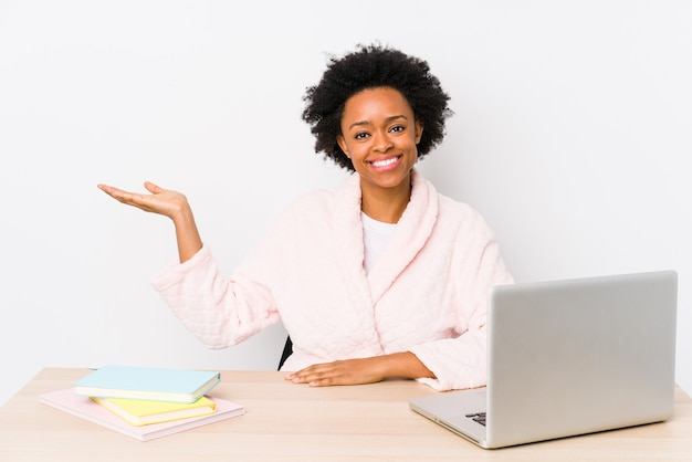 Mujer afroamericana de mediana edad que trabaja en casa aislada mostrando un espacio de copia en una palma y sosteniendo otra mano en la cintura.