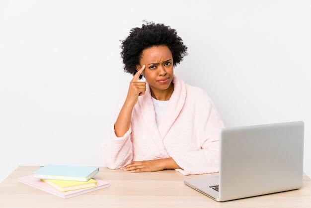 Mujer afroamericana de mediana edad que trabaja en casa señalando el templo con el dedo, pensando, centrado en una tarea.