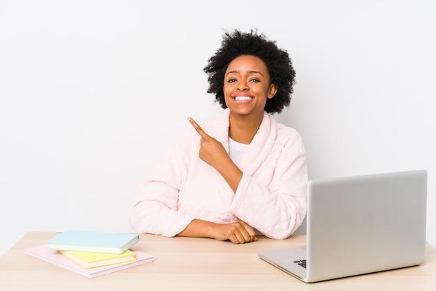 Mujer afroamericana de mediana edad trabajando en casa sonriendo y señalando a un lado, mostrando algo