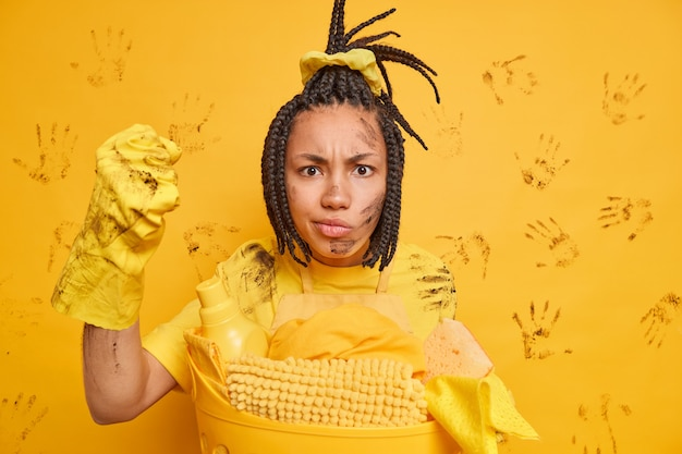 Mujer afroamericana molesta aprieta el puño mira con enojo a la cámara posa sucia cerca de la canasta de ropa ha peinado rastas aisladas sobre pared amarilla