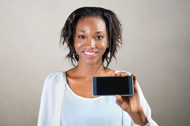 Mujer afroamericana mostrando un teléfono móvil