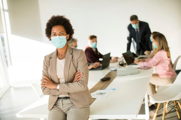 Mujer afroamericana en oficina usar máscara como protección contra coronavirus