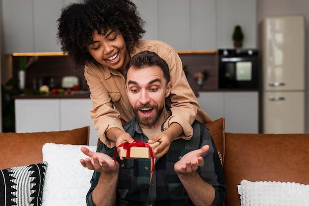 Mujer afroamericana ofreciendo un regalo a su novio