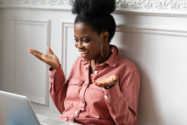Mujer afroamericana con peinado afro trabajando en una computadora portátil, gesticulando con las manos, mirando la webcam y charlando