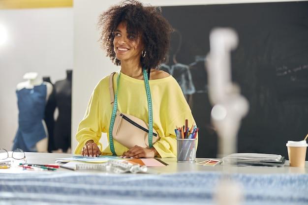 Mujer afroamericana pensativa con cinta métrica en la mesa en la clase de costura