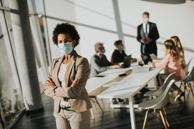 Mujer afroamericana de pie en la oficina y usar máscara como protección contra el virus corona