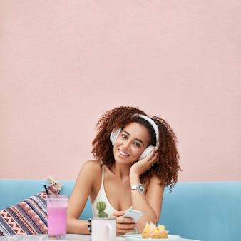 Mujer afroamericana de piel oscura alegre positiva vestida de manera informal, amante de la música, escucha canciones de la lista de reproducción, rodeada de un cóctel fresco