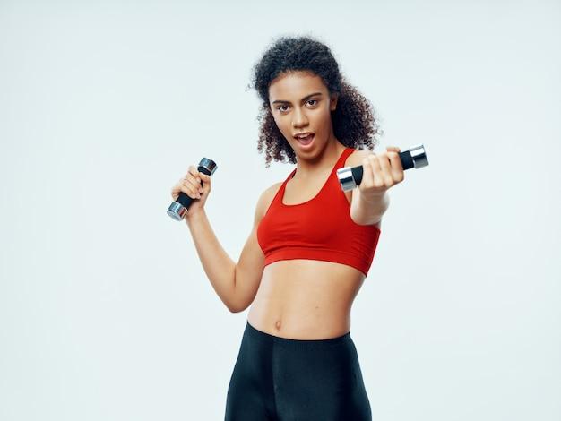 Mujer afroamericana de piel oscura posando en un chándal y haciendo deporte en el estudio