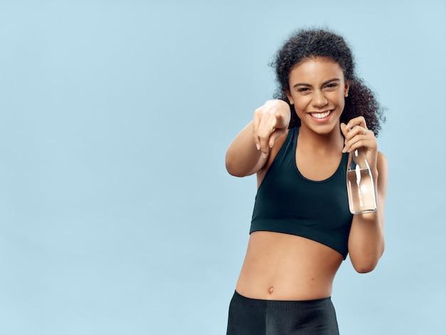 Mujer afroamericana de piel oscura posando en un chándal y haciendo espacio deportivo