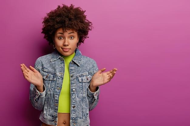 Una mujer afroamericana sin pistas y dudosa extiende las palmas de las manos con vacilación, no puede tomar una decisión, usa una chaqueta vaquera y un top, tiene una mirada desconcertada, posa sobre una pared violeta vibrante, copia el área del espacio a un lado