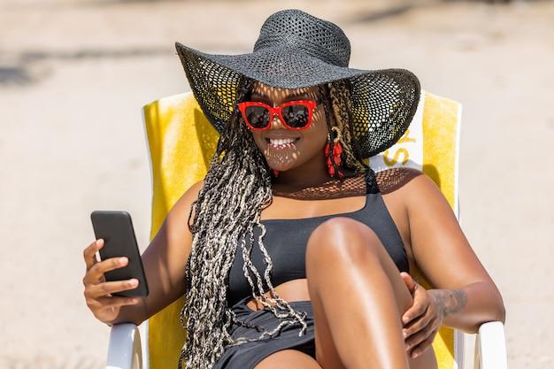 Mujer afroamericana en la playa con teléfono relajándose en una tumbona con un sombrero negro y gafas de sol. mujer adulta alegre disfrutando de un día de verano en la playa.