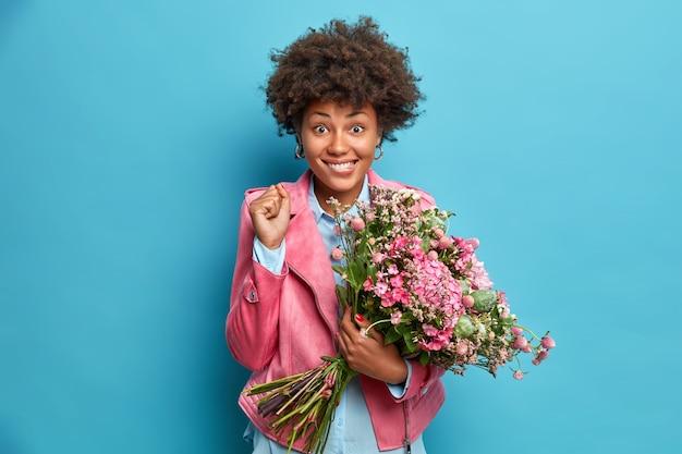La mujer afroamericana positiva aprieta los puños celebra la obtención de flores en el día internacional de la mujer posa con ramo