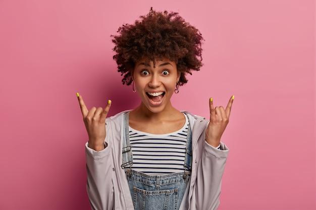 Una mujer afroamericana positiva hace un símbolo de rock con las manos en alto, exclama con alegría, dice vamos a sacudir mi mundo, disfruta de un evento agradable dedicado al heavy metal, usa una cazadora informal, posa sola en interiores