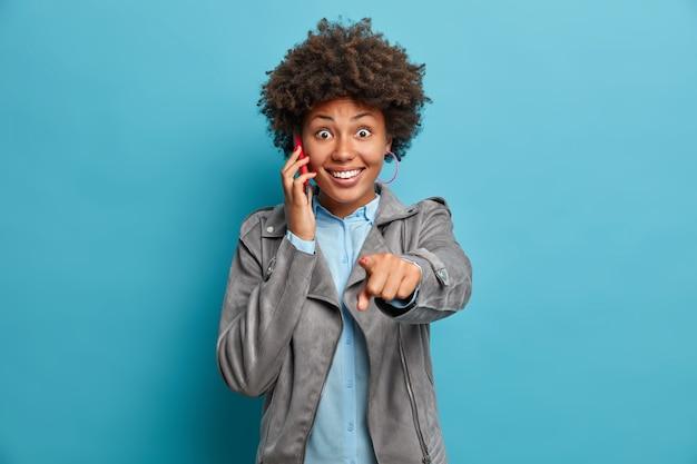 Una mujer afroamericana positiva indica directamente a la cámara que tiene una conversación telefónica y sonríe ampliamente