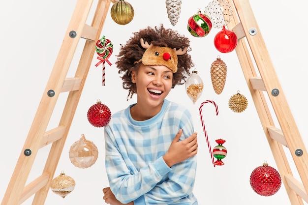 Una mujer afroamericana positiva está llena de sonrisas de felicidad y muestra unos dientes perfectos blancos, usa ropa de dormir cómoda, mira poses a un lado