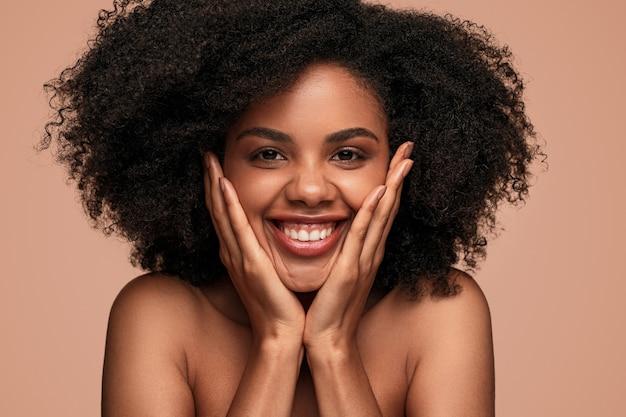 Mujer afroamericana positiva con piel sana mirando a la cámara