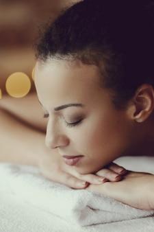 Mujer afroamericana que recibe un masaje relajante en el spa