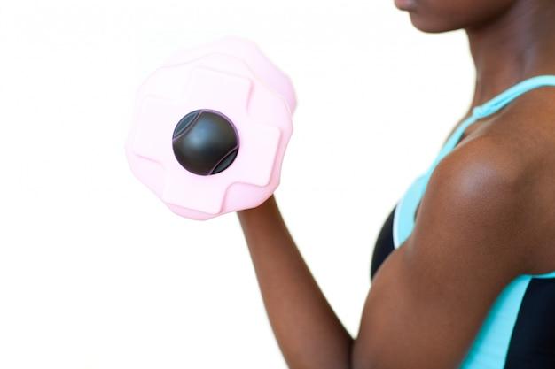 Mujer afroamericana que se resuelve con pesa de gimnasia