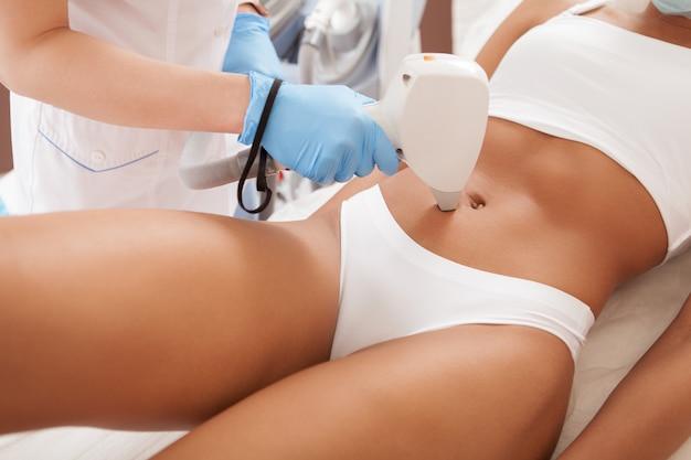 Mujer afroamericana recibiendo tratamiento de depilación láser