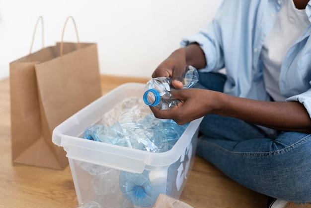 Mujer afroamericana reciclando para un mejor medio ambiente