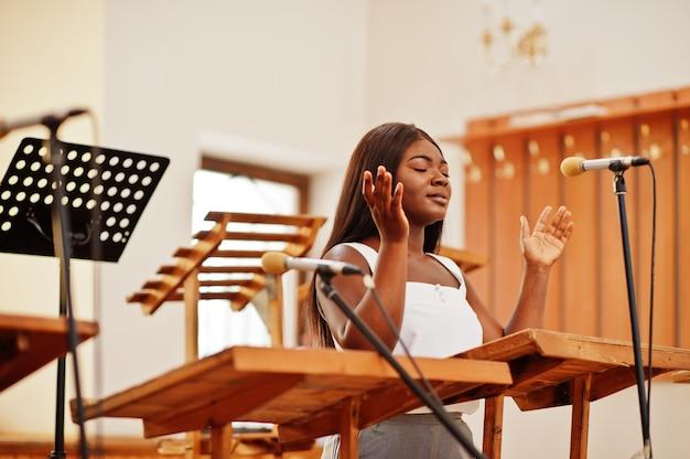 Mujer afroamericana rezando en la iglesia. los creyentes meditan en la catedral y en el tiempo espiritual de oración. chica afro cantando y glorificando a dios en coros.