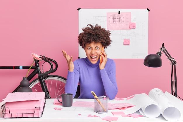 La mujer afroamericana rizada joven enojada exclama en voz alta que la conversación telefónica levanta la mano y grita de las poses de ira en el espacio de coworking que se irrita por cometer un error en el boceto del edificio