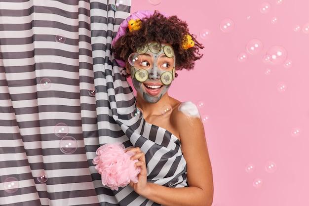 Mujer afroamericana rizada positiva con cabello rizado aplica mascarilla de arcilla con pepinos para rejuvenecimiento de la piel sostiene esponja de ducha toma ducha en el baño