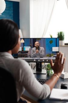 Mujer afroamericana saludo empresario remoto con ordenador portátil webcam